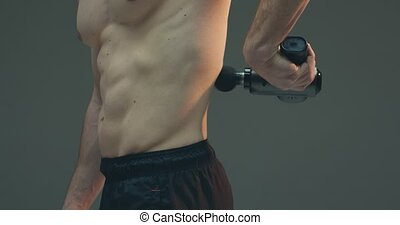 Deep tissue percussion massager, sportsman guy massaging lower back for pain relief on gray studio background. High quality 4k footage