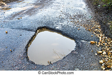 Deep, waterfilled pothole in the road - Severe winter damage...
