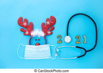Deer antlers in a medical mask and stethoscope with numbers 2021 a  on a blue background.