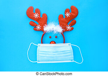 Deer face made from a deer antler hoop and a Christmas toy in a medical mask on a blue background.