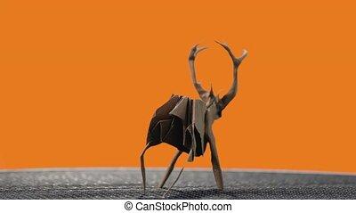Deer figurine on orange background. Beautiful handmade art, origami or paper folding. Crafts and creative skills.