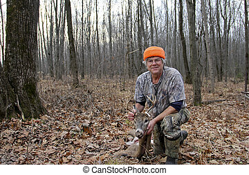 deer hunter with a whitetail buck skinned for harvest with trees and leaves as a background