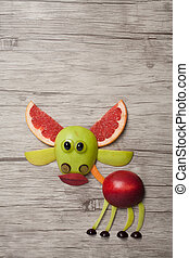 Deer made with fruits on wooden background