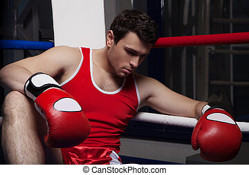 Defeated boxer. Disappointed young boxer sitting on the...