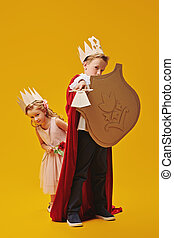 Cute boy and little girl play Prince and Princess together. Childhood dreams. Fantasy, imagination. Studio portrait on a yellow background.
