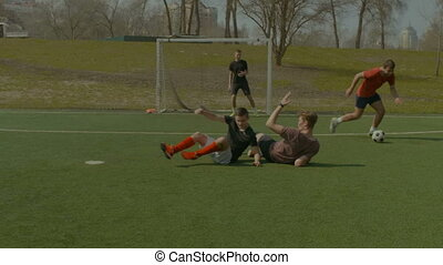 Defender committing a foul during football match - Soccer...