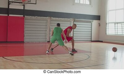 Defender stealing basketball from opposing player - Athletic...