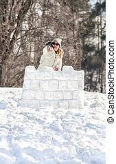 Defense of a snow fort. Young woman enjoying winter and ...