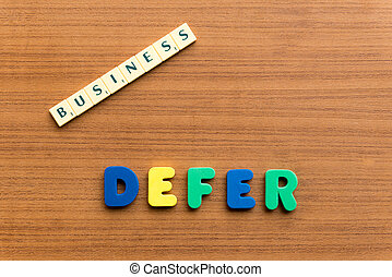 defer colorful word on the wooden background