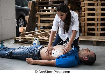 defibrillation electrodes - rescuer applying defibrillator...