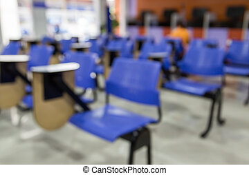 Defocus of tables and blue chairs in empty classroom