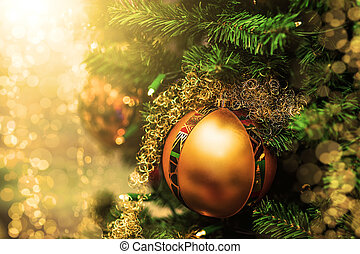 golden Christmas ball on  branches of fir tree