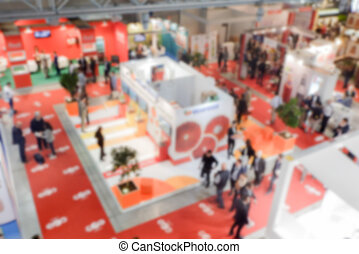 Defocused background of a trade show with people visiting...