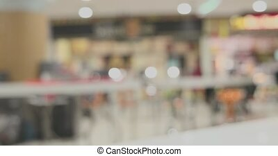 Defocused background of big mall food court hall showing...