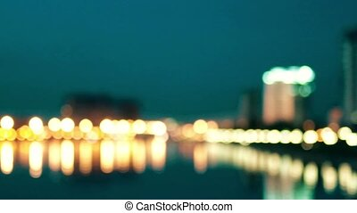Defocused background of city view from riverbank. Nighttime on the city waterfront. Streetlamps row reflection in water and  flow of cars, image in yellow-green toning