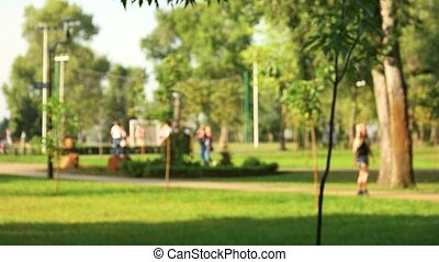 Defocused background of summer park with walking people.
