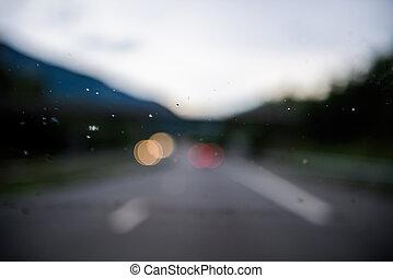 Defocused bokeh focus blur on the raindrops on the car