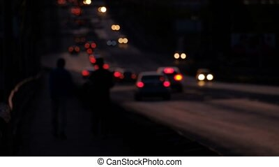 Defocused car lights and two silhouttes of pedestrean