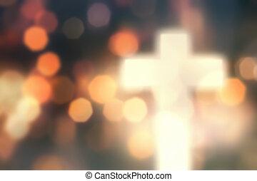 Defocused christian cross against light background