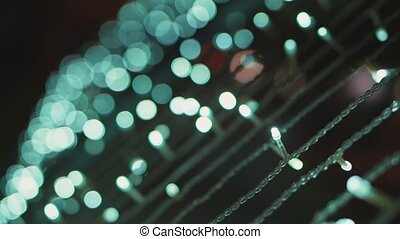 Defocused Christmas lights at night outside. Decorations and garlands on the streets of the city.