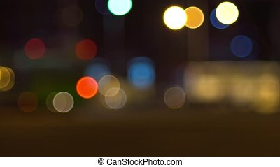 defocused city street with passing cars late in the evening, at night