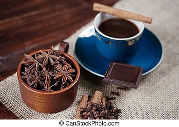 Defocused coffee with ansie and cinnamon on table