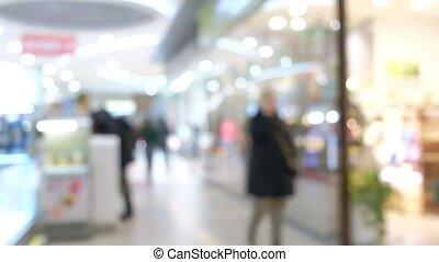 Defocused customers walking along shop windows indoors