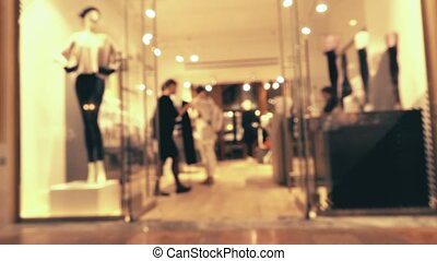 Defocused female customer and sales assistant in the stockings shop in a modern shopping mall