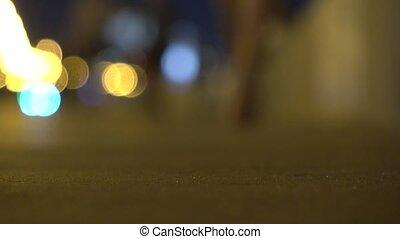 Defocused girl in high heels walking at the camera at night. Shallow focus 4K shot