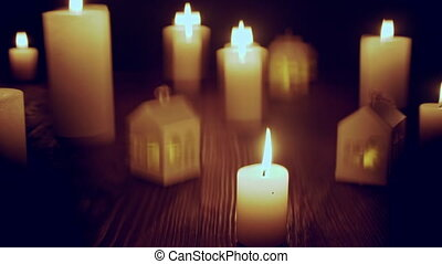 Defocused glowing candles and blinking decorative houses on...