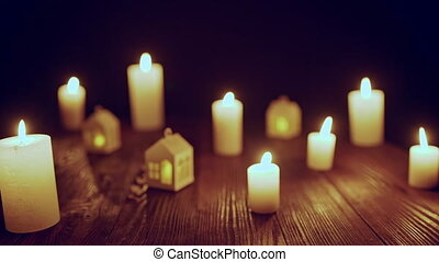 Defocused glowing candles and blinking decorative houses -...