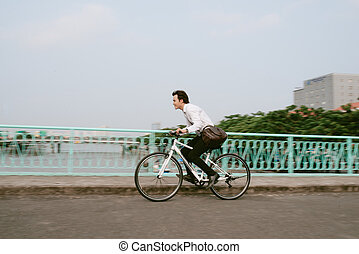 Defocused image of an active businessman riding a bicycle on the way to job