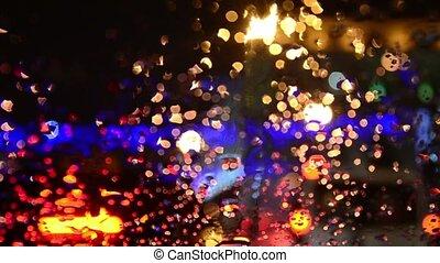 Defocused lights. Driving on a rainy highway, cars braking....