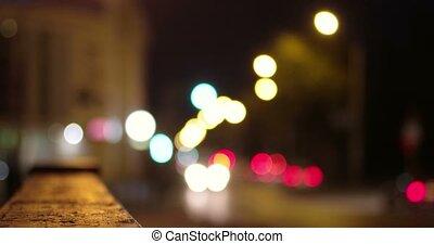 Defocused lights of cars in night city.