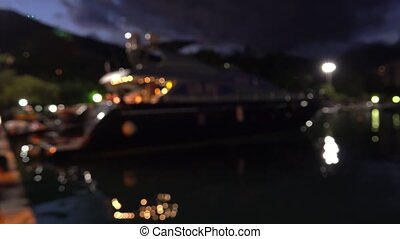 Defocused moored luxury motor yacht at marina at night -...
