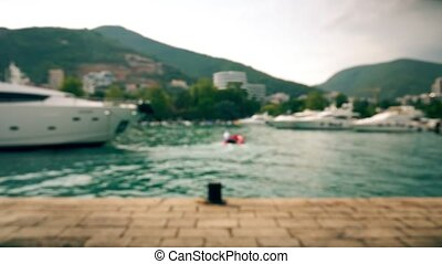 Defocused moored luxury motor yachts and red motor boat at...