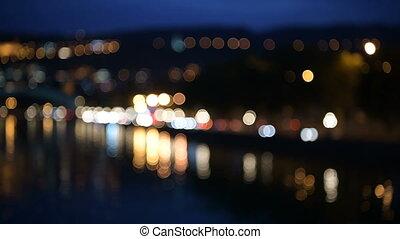 Defocused night city road: river, bridge, cars moving and...