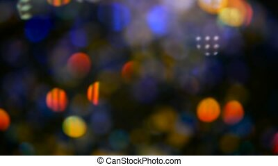 Defocused shimmering multicolored glitter confetti, black background. Holiday abstract festive bokeh light spots.