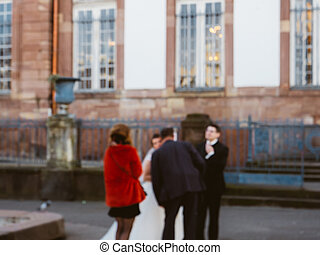 Defocused silhouette of friends in front of the city hall during a wedding congratulating