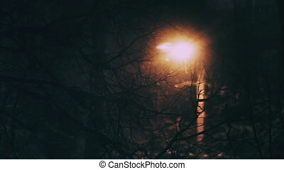 Defocused snow falling on the background of street lamp of an apartment house in the city at night.