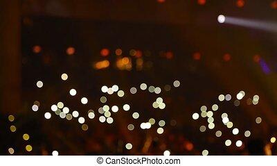 Audience is shining with flashlights of phones. - Defocused...
