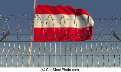 Defocused waving flag of Austria behind barbed wire fence....