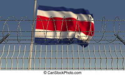 Defocused waving flag of Costa rica behind barbed wire fence. 3D rendering