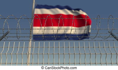 Defocused waving flag of Costa rica behind barbed wire...