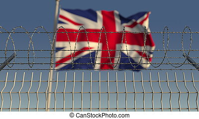 Defocused waving flag of Great Britain behind barbed wire ...