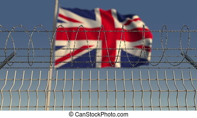 Defocused waving flag of Great Britain behind barbed wire fence. Loopable 3D animation