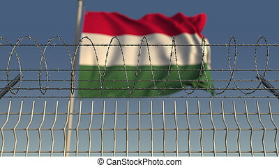 Defocused waving flag of Hungary behind barbed wire fence. 3D rendering
