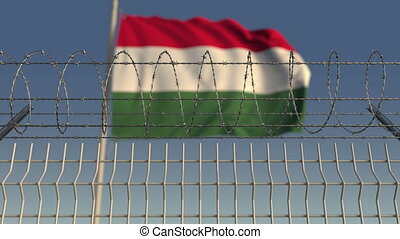 Defocused waving flag of Hungary behind barbed wire fence. Loopable 3D animation