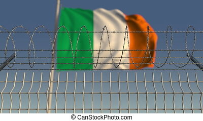 Defocused waving flag of Ireland behind barbed wire fence....