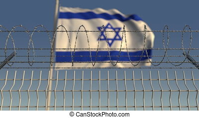 Defocused waving flag of Israel behind barbed wire fence....